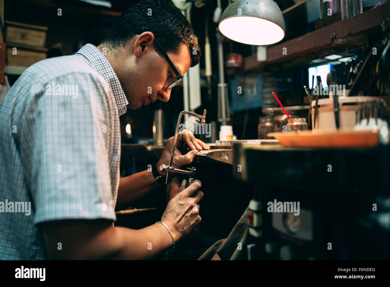 Handyman working on workbench with tools - Stock Image