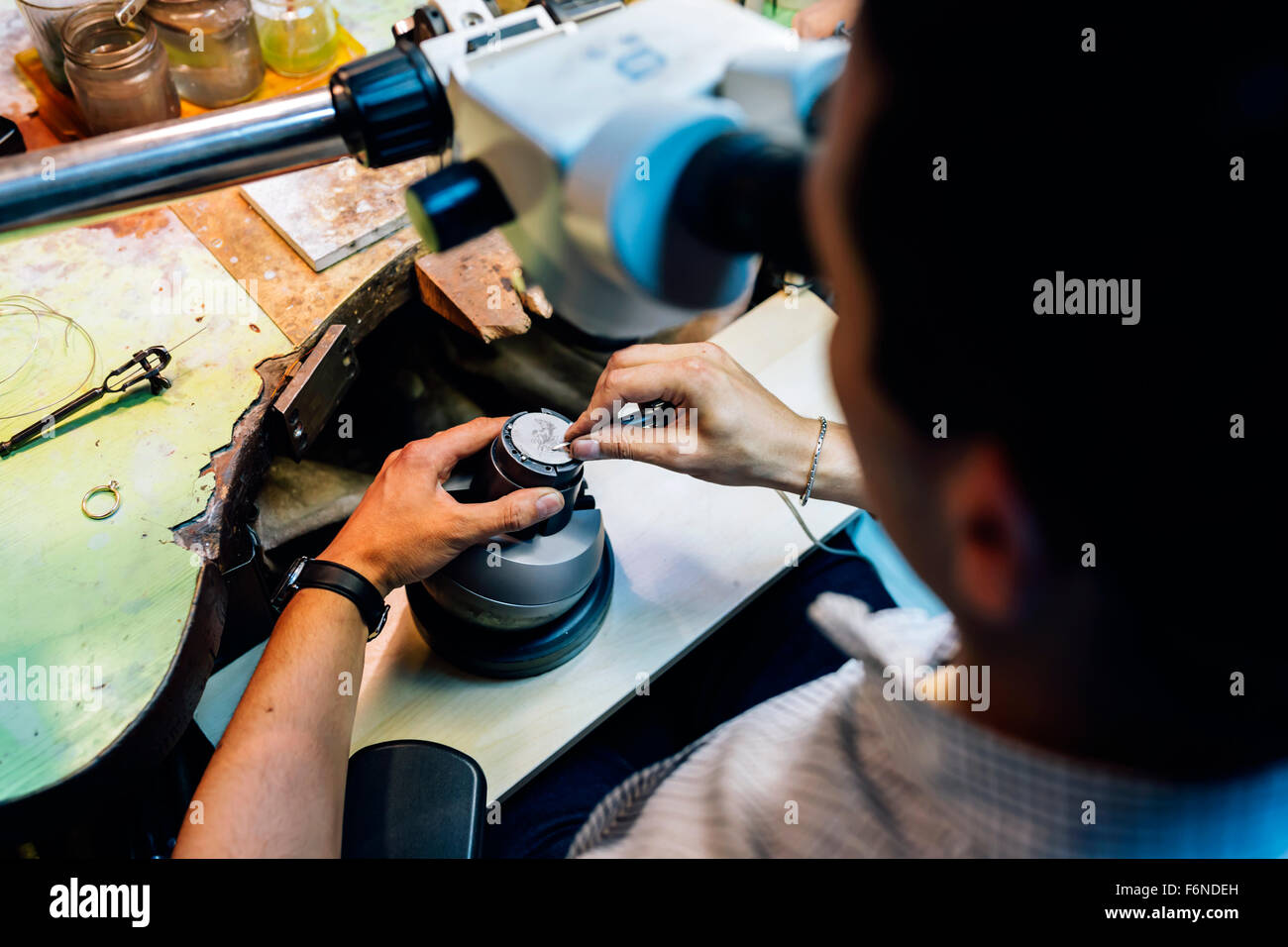 Jeweler working on metals with optical device that allows for precision work - Stock Image