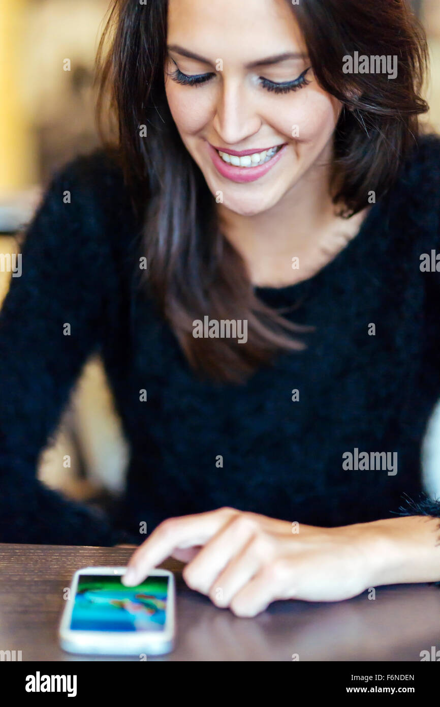 Beautiful brunette tapping phone - Stock Image