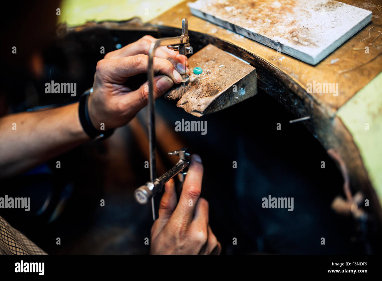 Jeweler using saw to create jewelry - Stock Image
