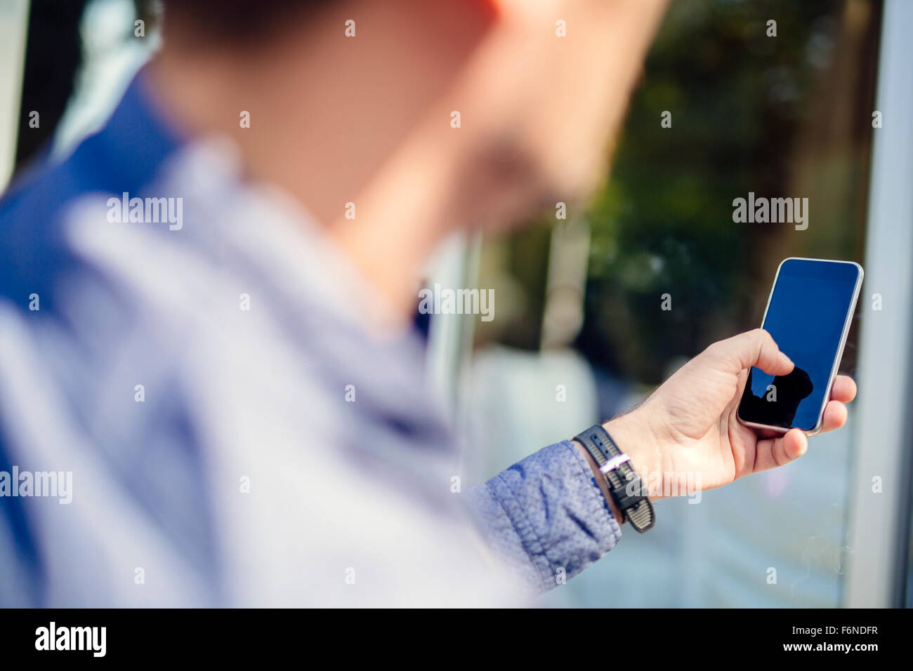 Man holding phone outdoors and tapping it - Stock Image