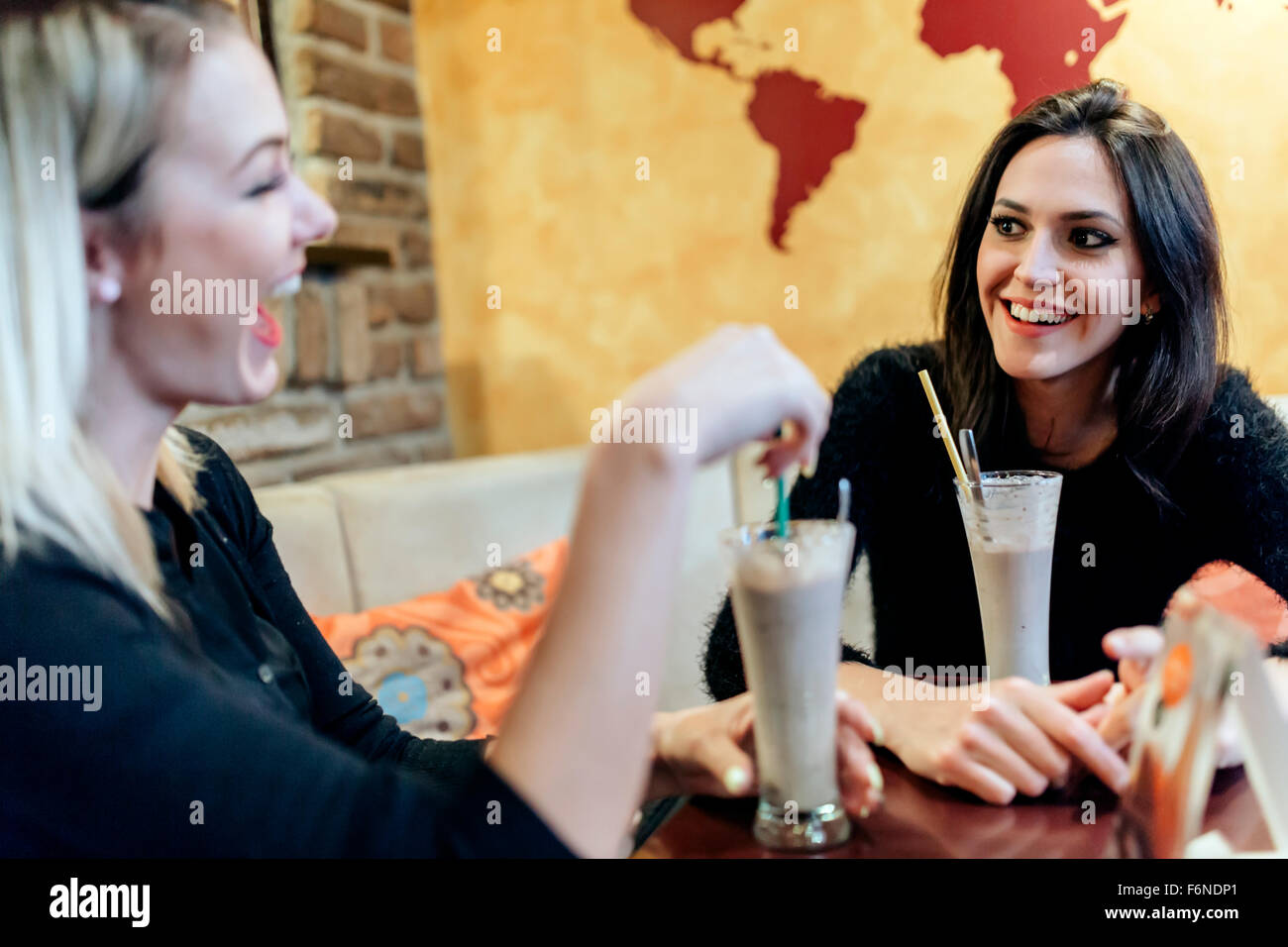 Two women drinking and talking in cafe while having a good time - Stock Image