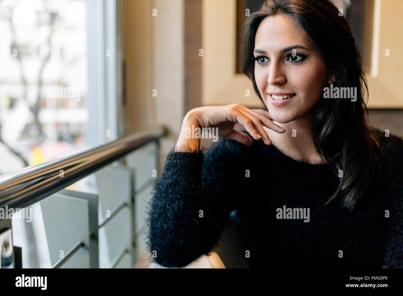 Pensive beautiful brunette looking out the window - Stock Image