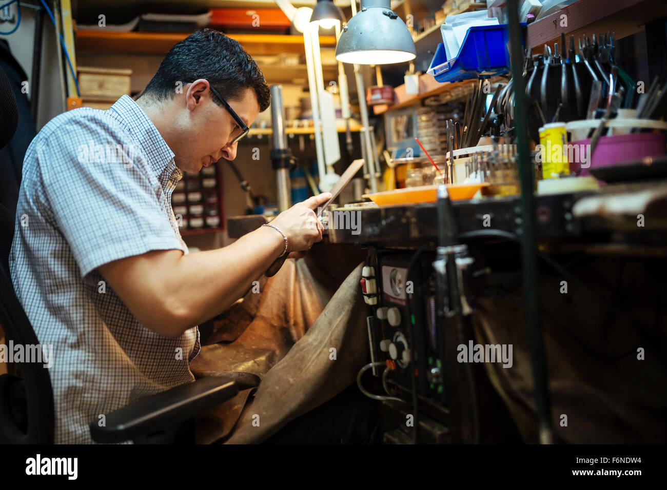 Goldsmith working on his workbench - Stock Image