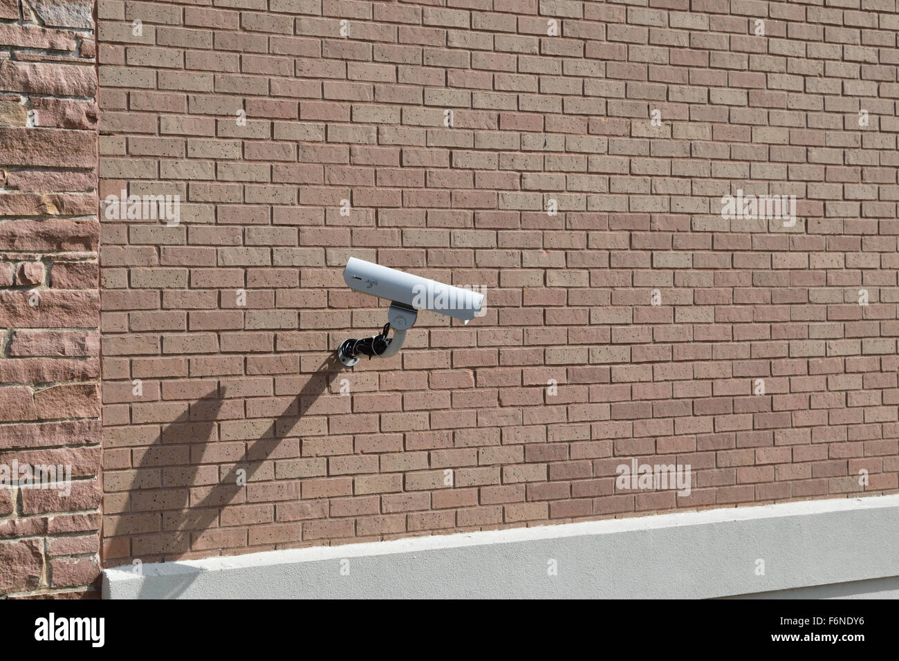 Security camera on the side of a brick building - Stock Image