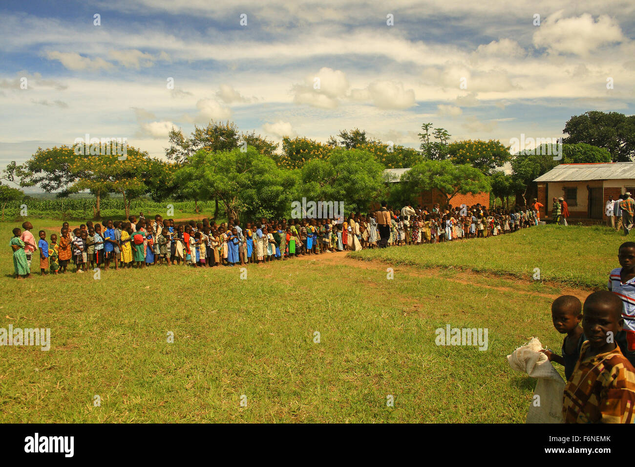 School children queuing for food from a feeding programme in the village of Nyombe, Malawi, Africa - Stock Image