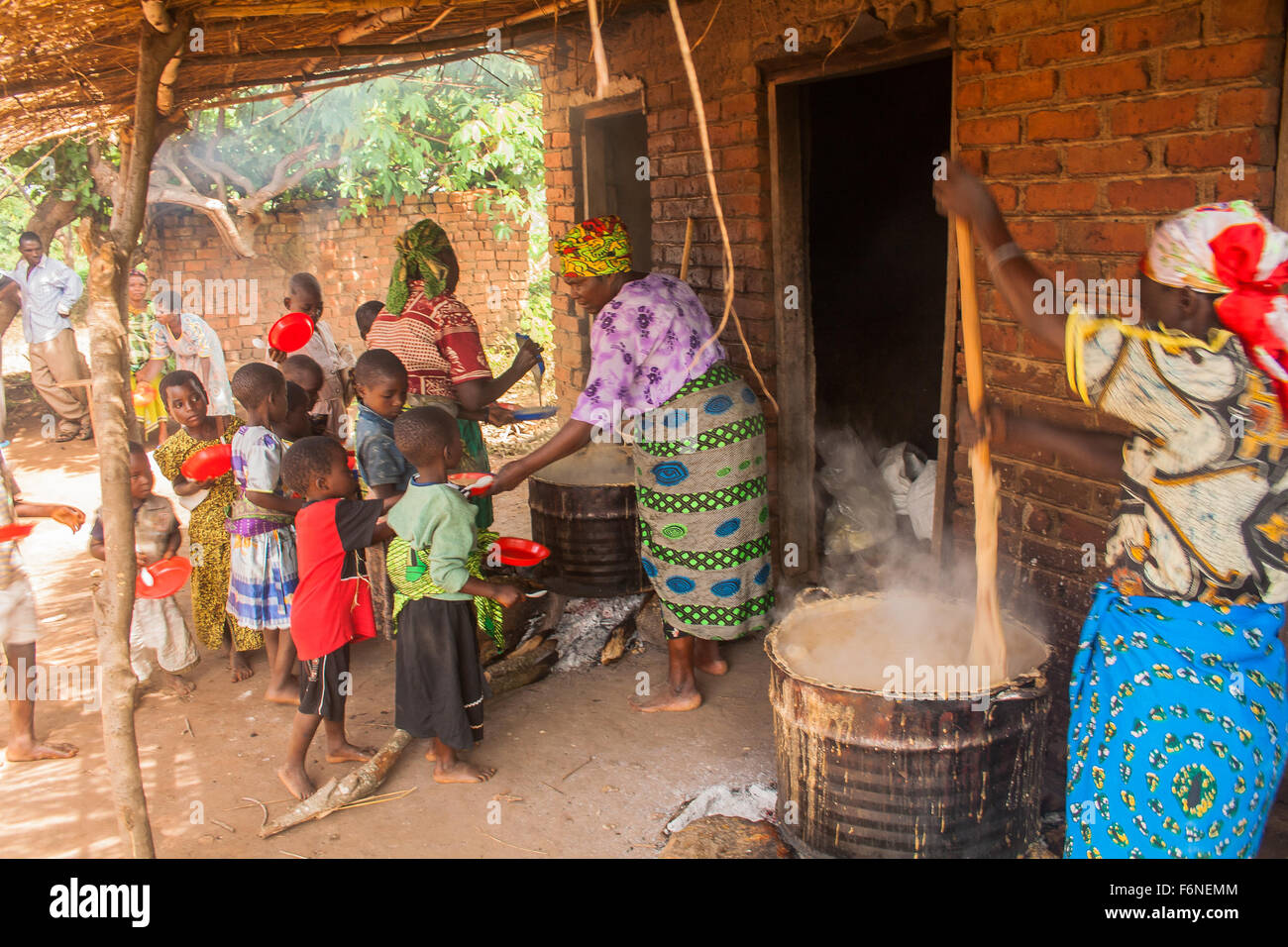 Women from the local church cooking food for school children in a time of hunger in the village of Nyombe, Dedza, - Stock Image