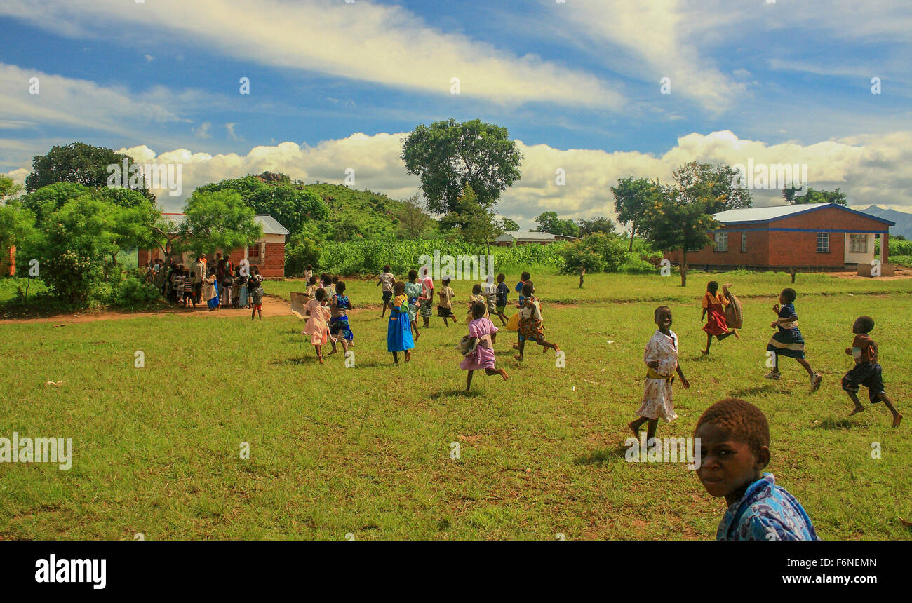 School children running to queue for food from a feeding programme in the village of Nyombe, Malawi, Africa - Stock Image