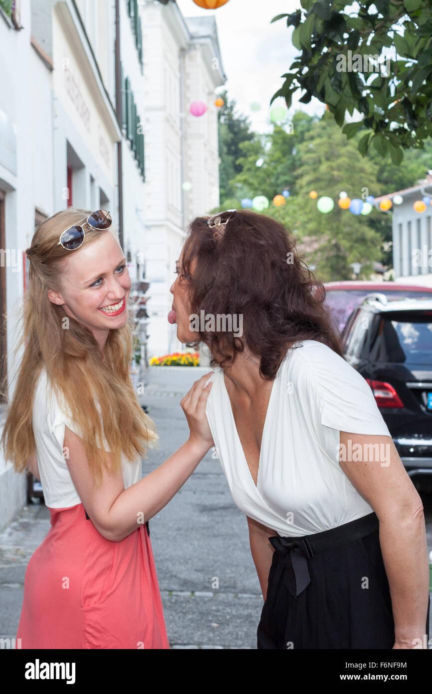 Two Playful Women Acting Childish on City Sidewalk Stock Photo