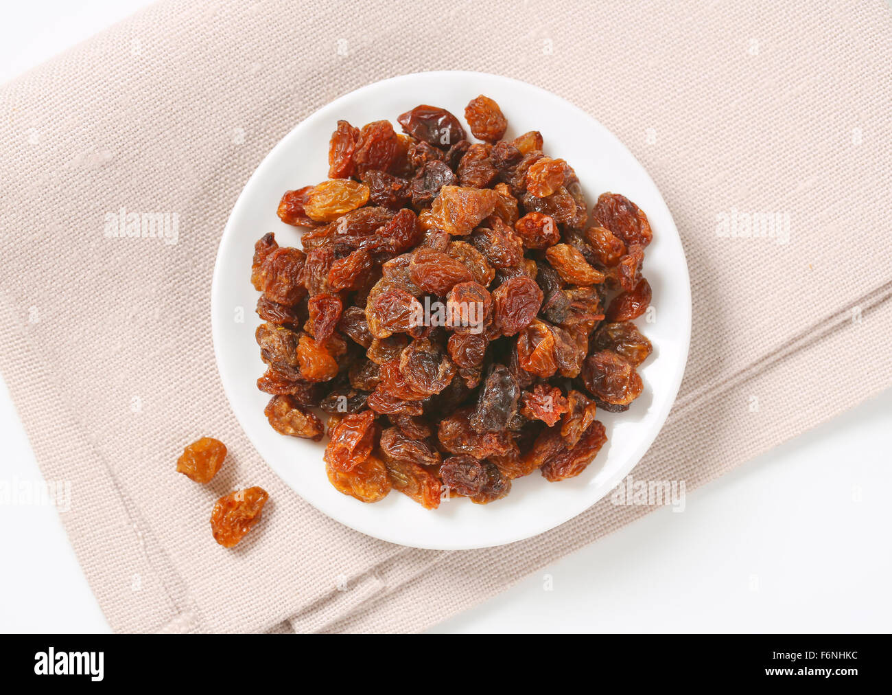 plate of raisins on beige place mat - Stock Image