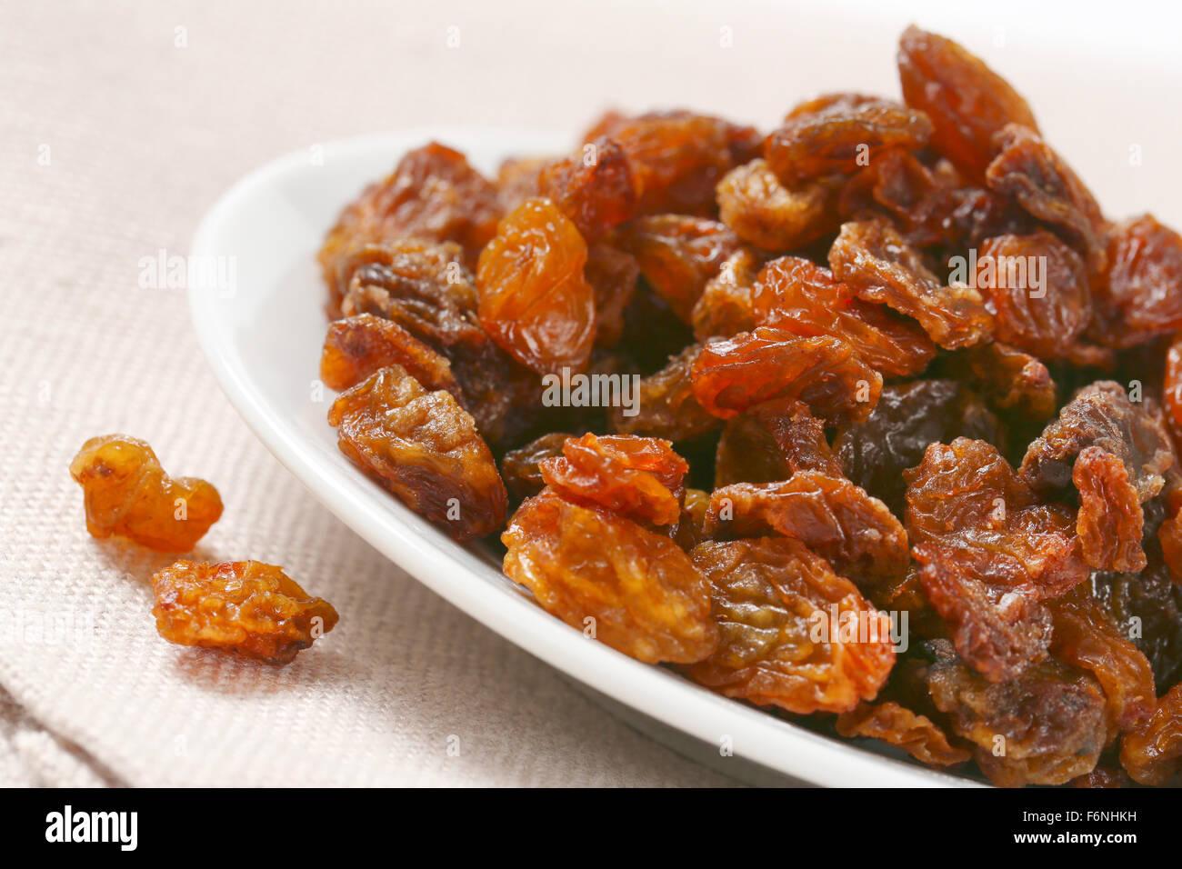 detail of raisins on white plate - Stock Image