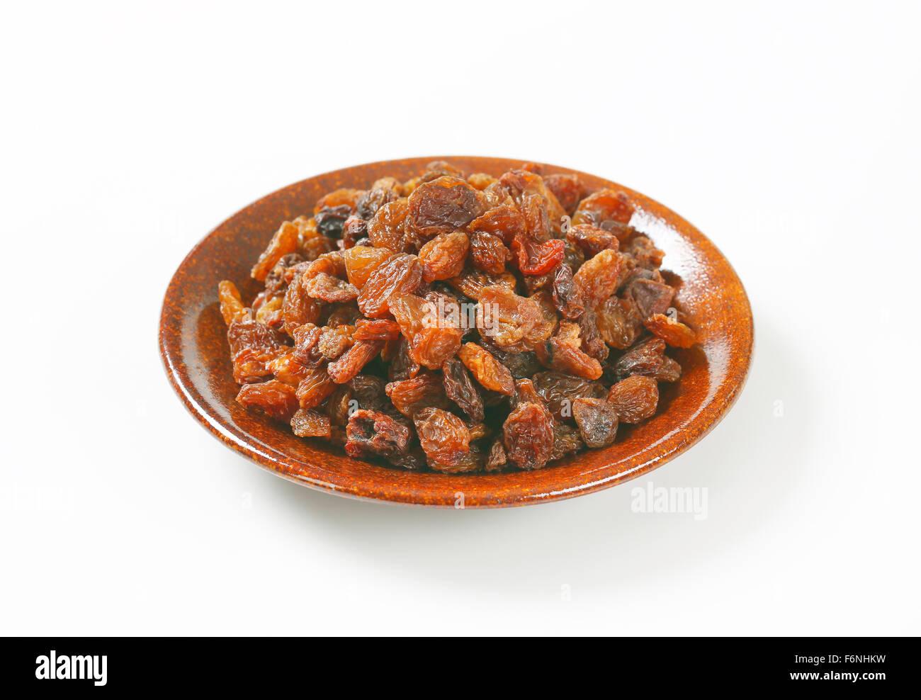 plate of raisins on white background - Stock Image