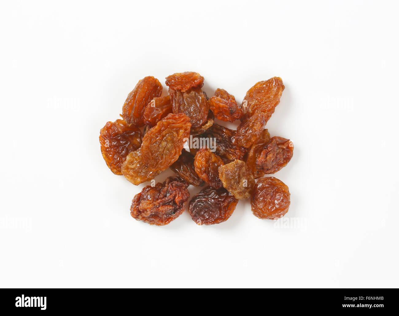 handful of raisins on white background - Stock Image