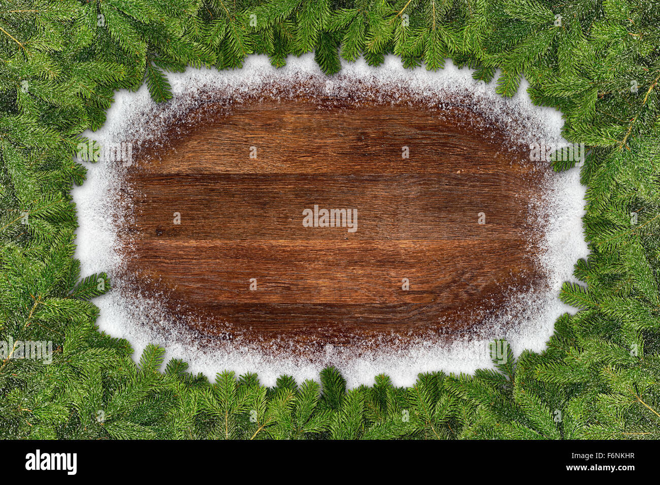 fir branches frame on wooden snowy background - Stock Image