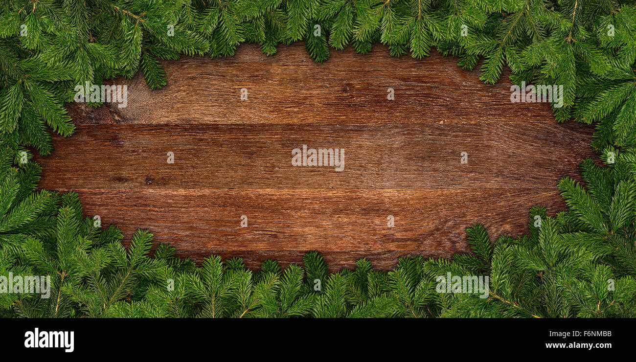 fir branches frame on wooden background - Stock Image
