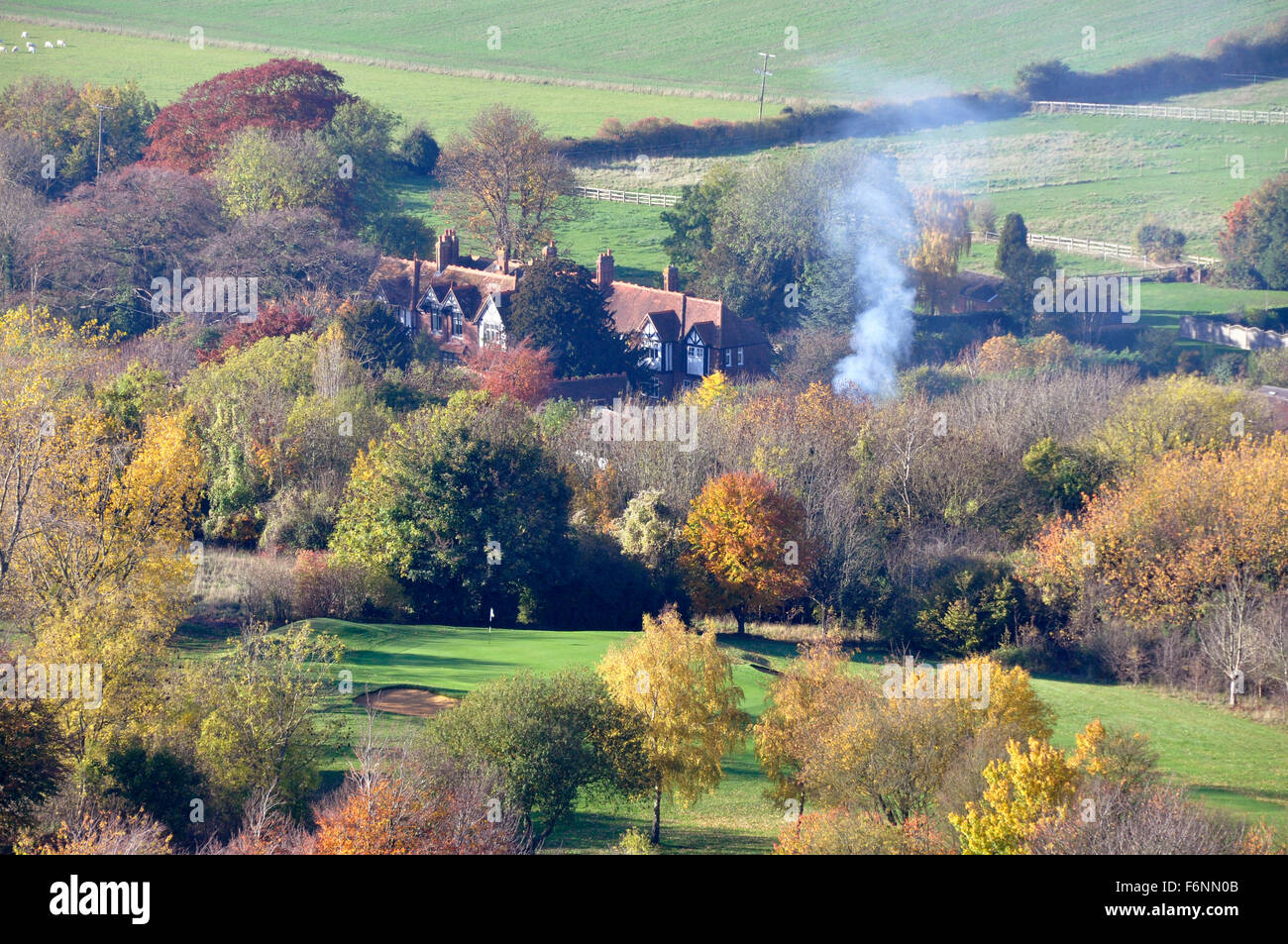 Bucks - Chiltern Hills - on Coombe Hill - view over autumn in the trees - cottages rooftops - drifting smoke from - Stock Image