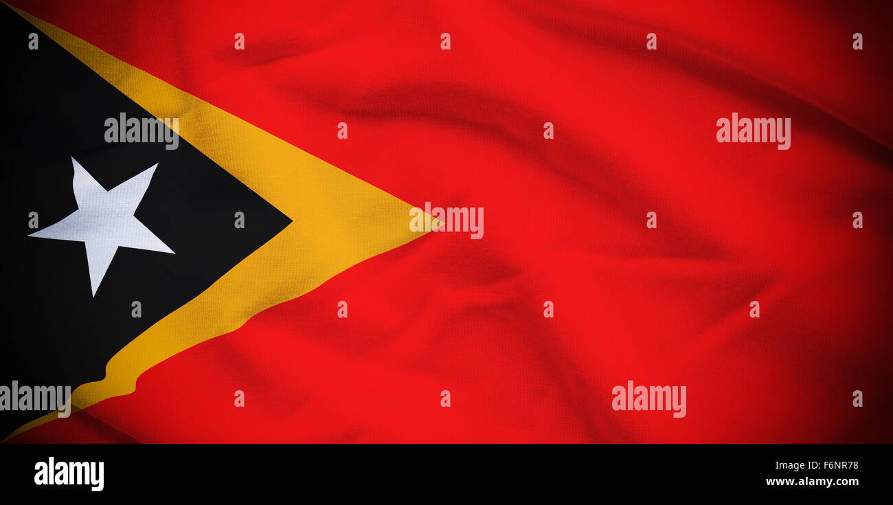 Wavy and rippled national flag of East Timor background. - Stock Image