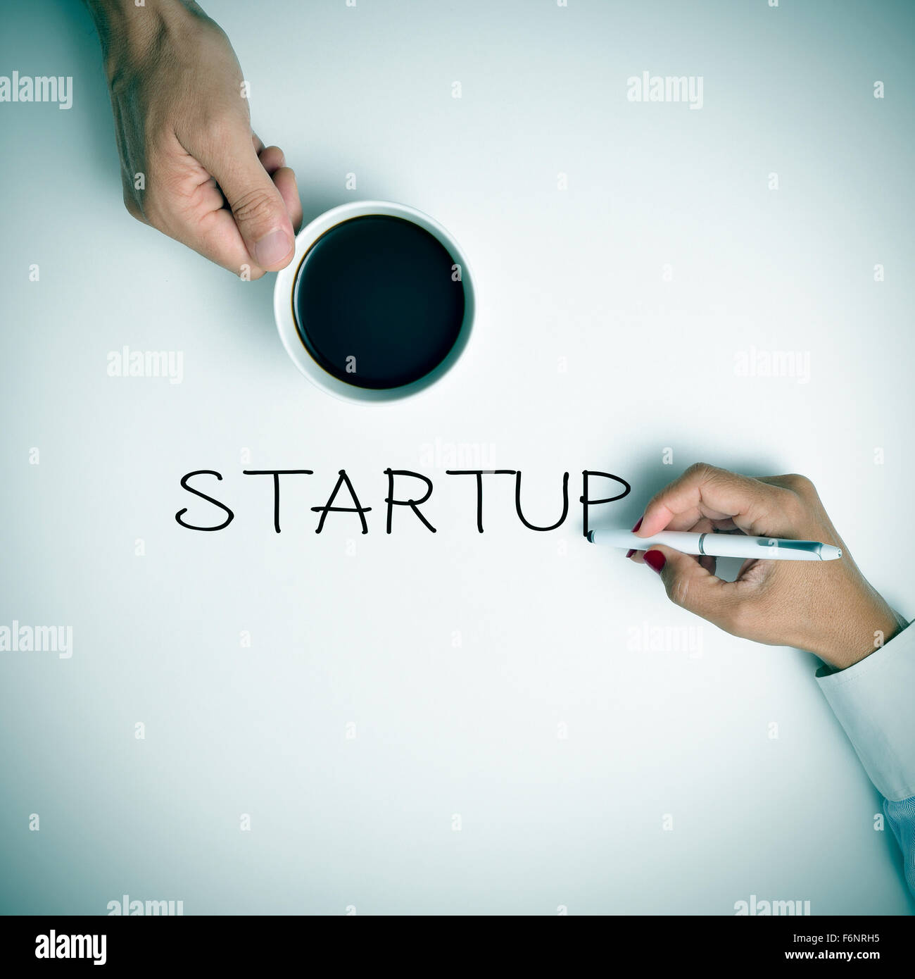 high-angle shot of a young man with a cup of coffee and a young woman writing the text startup with a pen - Stock Image