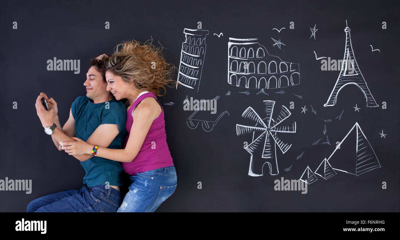 Young couple making a selfie with world attractions ilustrations behind. - Stock Image