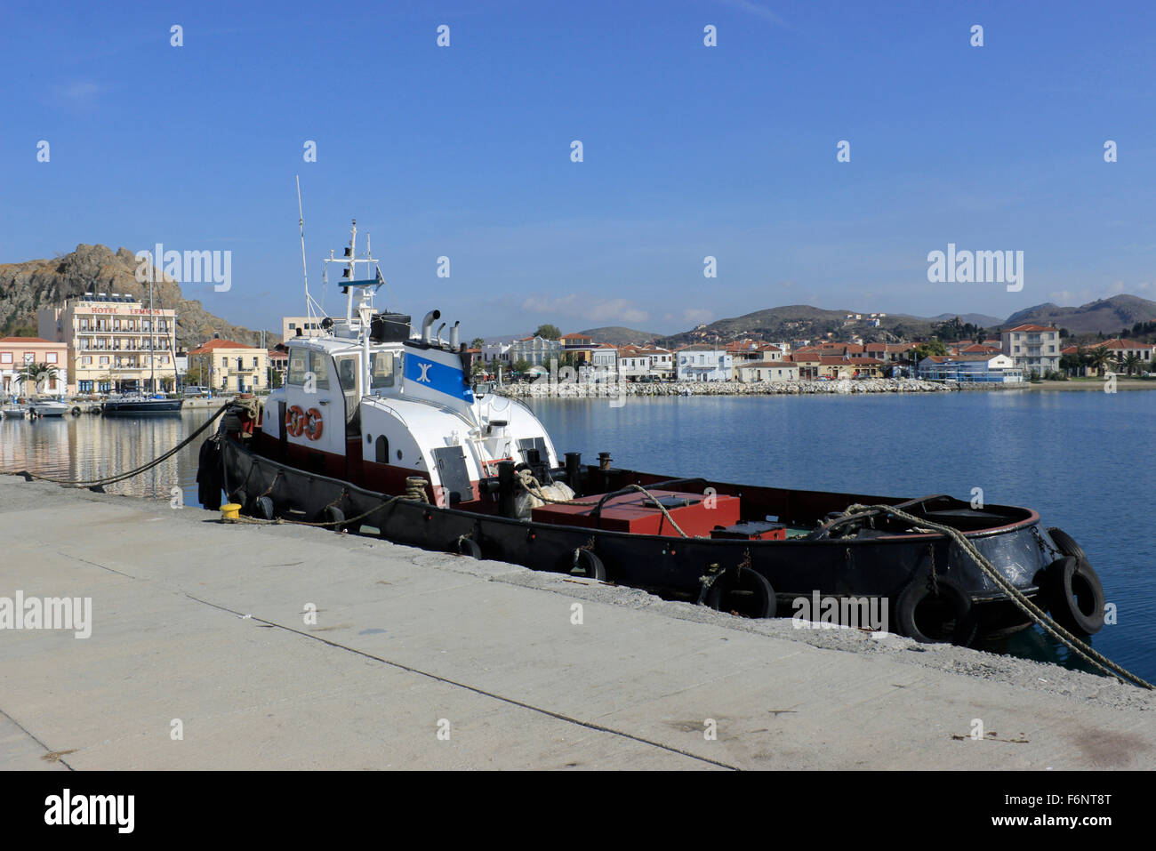 Anchored tug boat and Myrina's city port and quay (afar) view - Stock Image