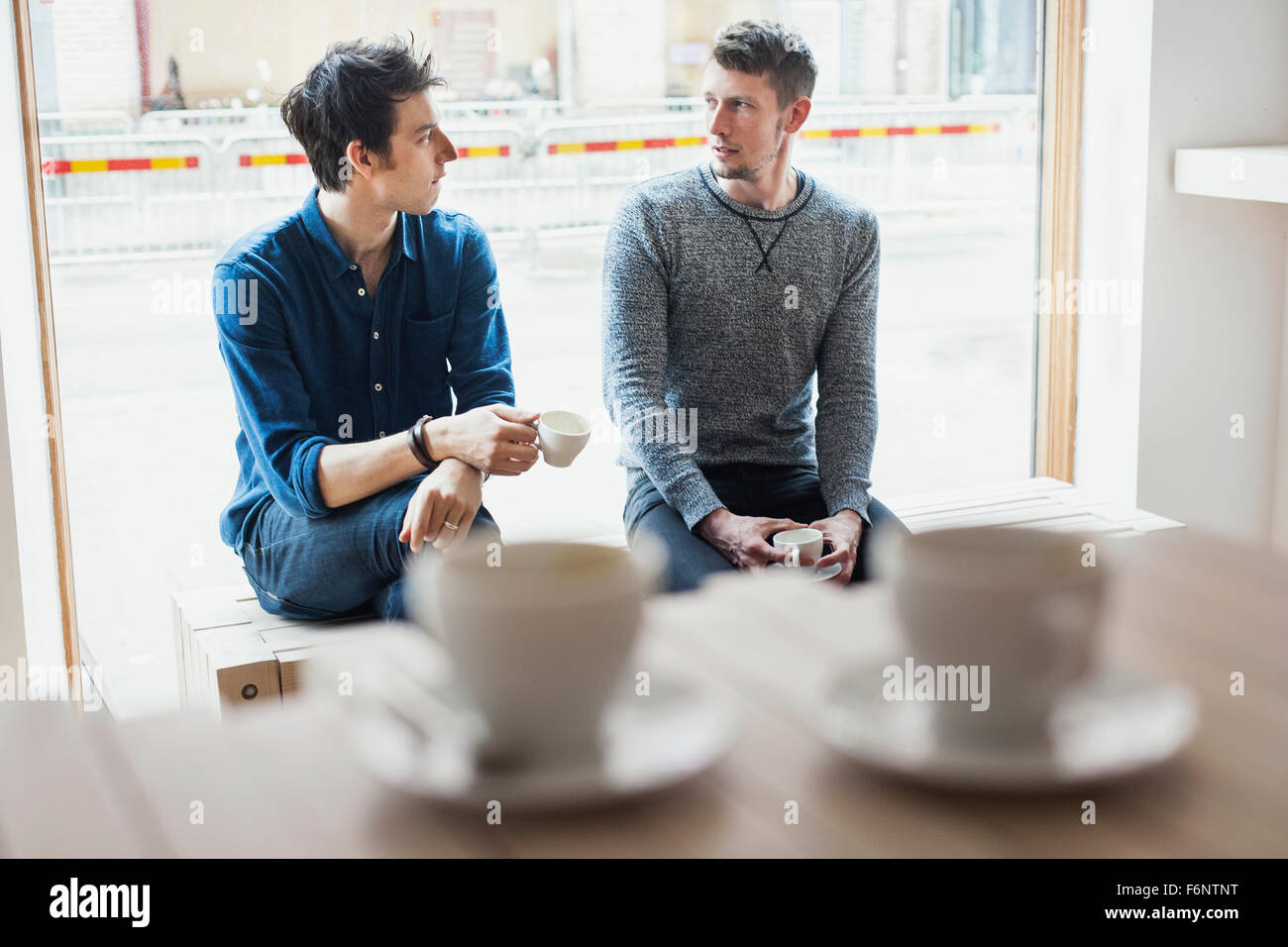 Friends conversing while sitting by window at cafeteria - Stock Image