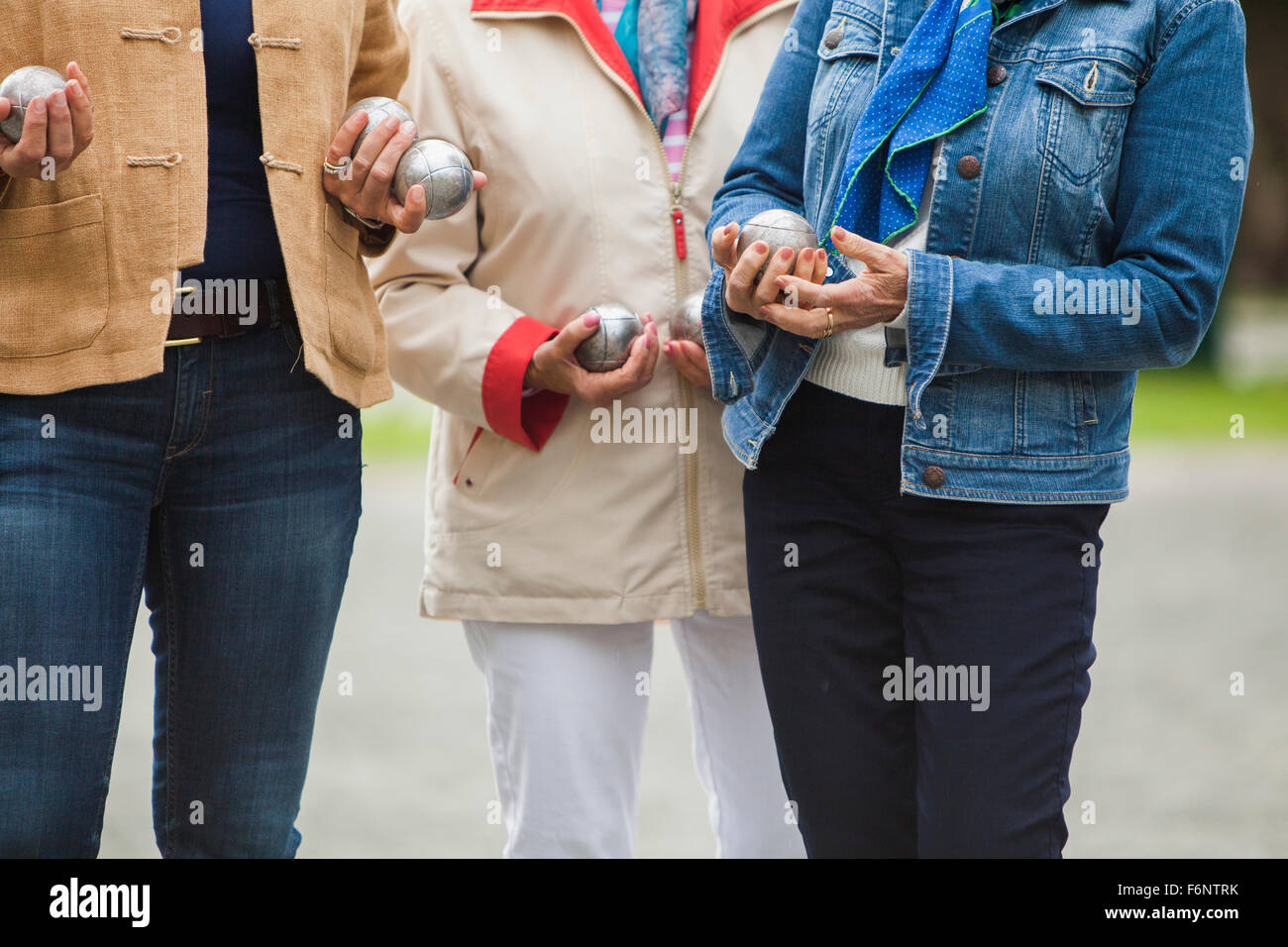 Close-up of senior women holding balls and standing at field - Stock Image