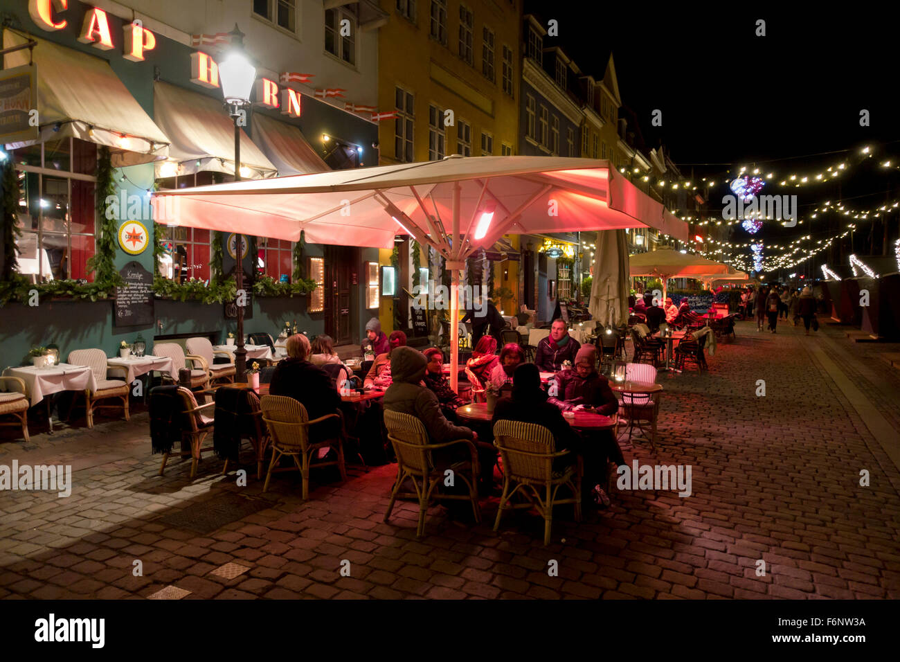 Heated outdoor serving at pavement restaurants and bars in a Christmas decorated and illuminated Nyhavn district - Stock Image