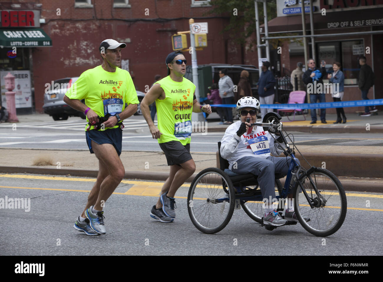 Runners accompany elderly disabled woman along 4th Ave in Brooklyn determined to pedal the full course of the NYC - Stock Image