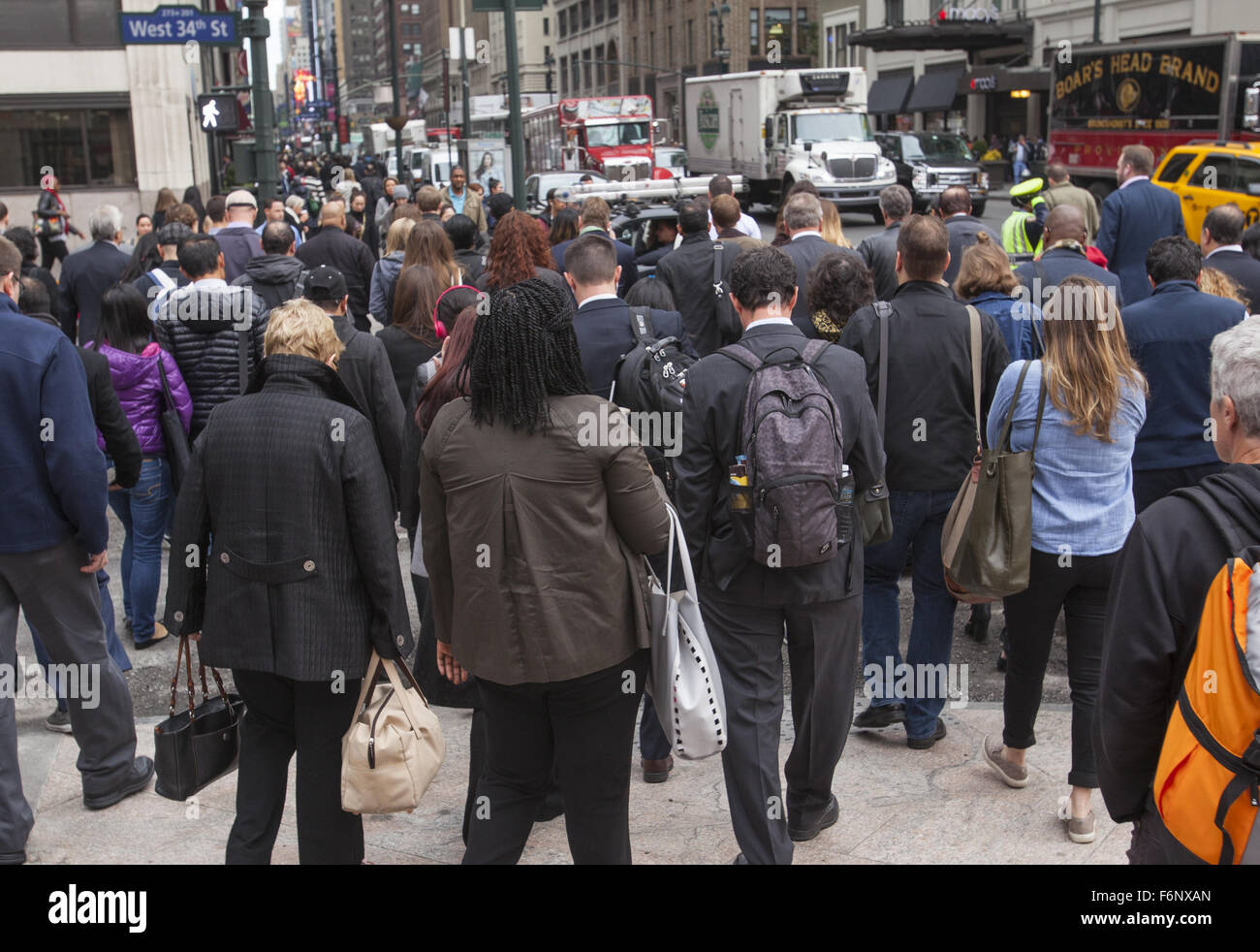 Morning rush hour crowds of office building workers cross 34th Street and 7th Avenue in Manhattan. - Stock Image