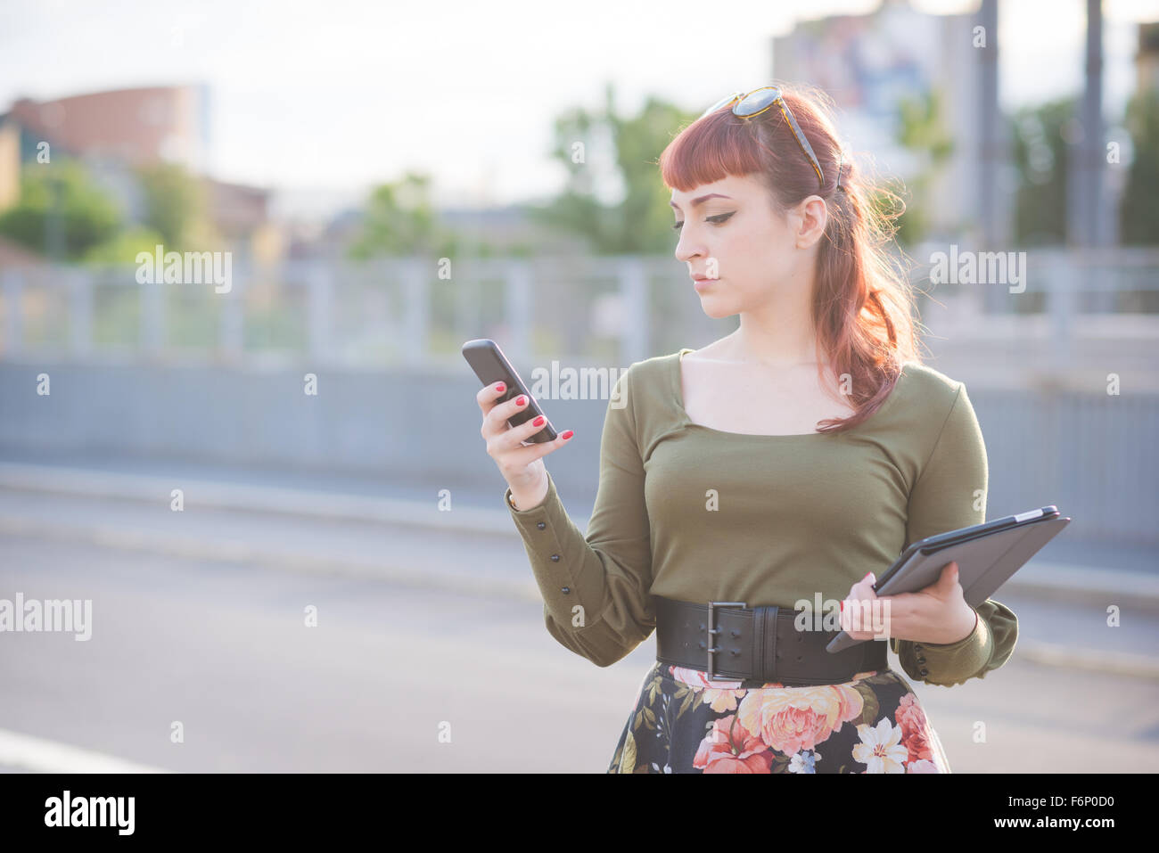Half length of young handsome caucasian redhead woman using a smartphone, looking downward and tapping the screen Stock Photo