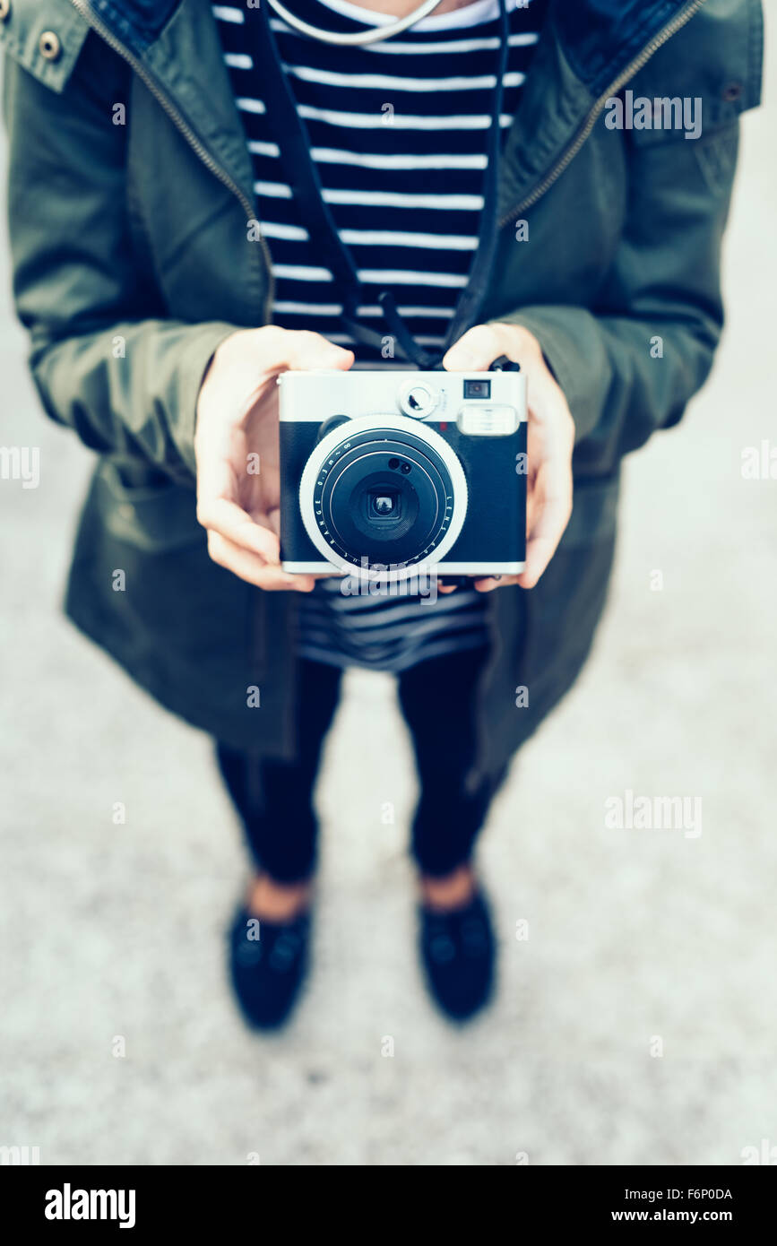 Young handsome woman holding a vintage camera - photography, creative concept - focus on the camera - Stock Image