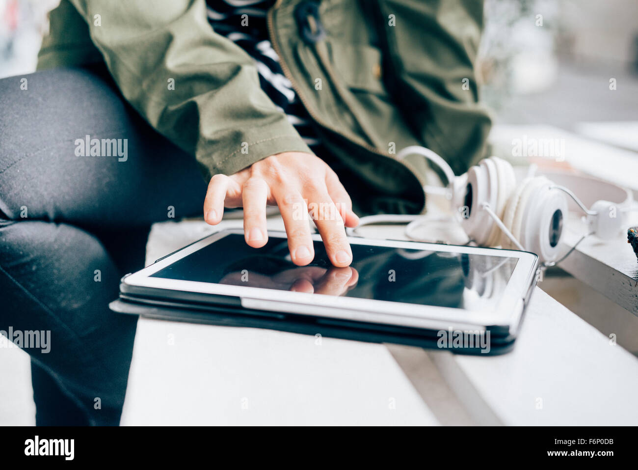 Close up on the hand of a young handsome woman tapping the screen of a laptop - technology, communication, social - Stock Image