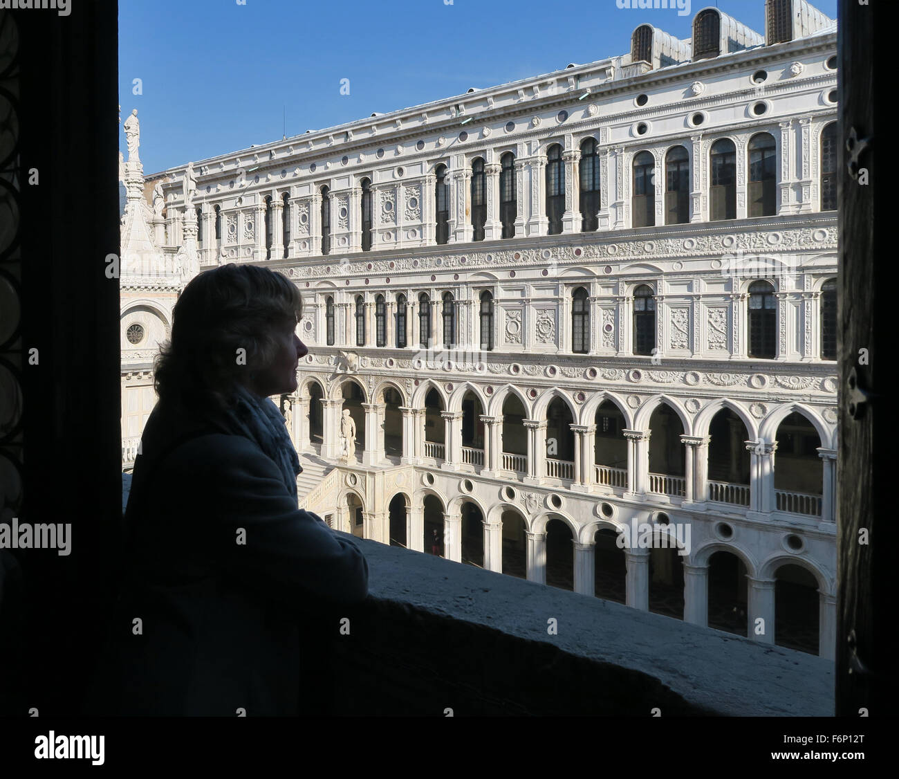 Tourist viewing the courtyard facade at the Doge's Palace at St Marks Square, San Marco, Venice. - Stock Image