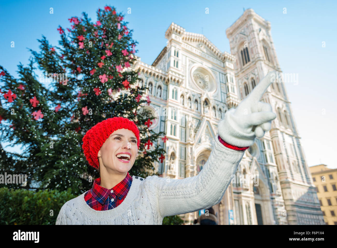 Happy young travel lover in white sweater pointing on something in front of traditional christmas tree near Duomo - Stock Image