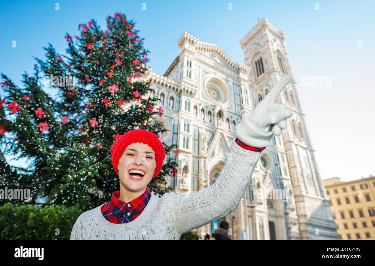 Hey, take a look! Happy young travel lover in white sweater pointing on something in front of traditional christmas Stock Photo