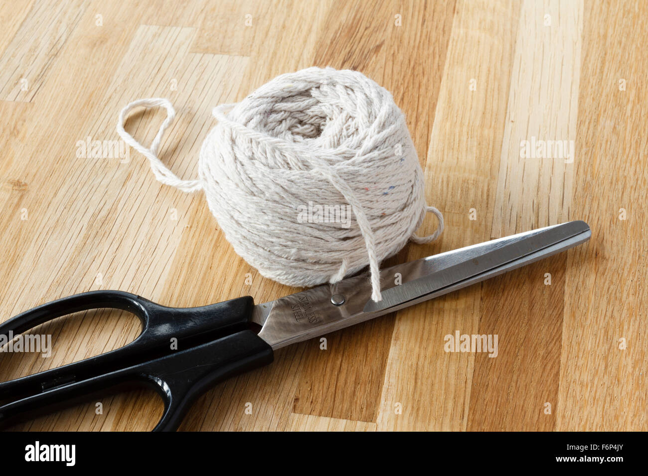 Ball of string and scissors on wooden table - Stock Image