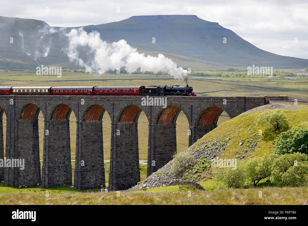 Ribblehead Viaduct. Steam train LMS Jubilee Class Leander 45690 crossing the viaduct below Ingleborough hill. - Stock Image