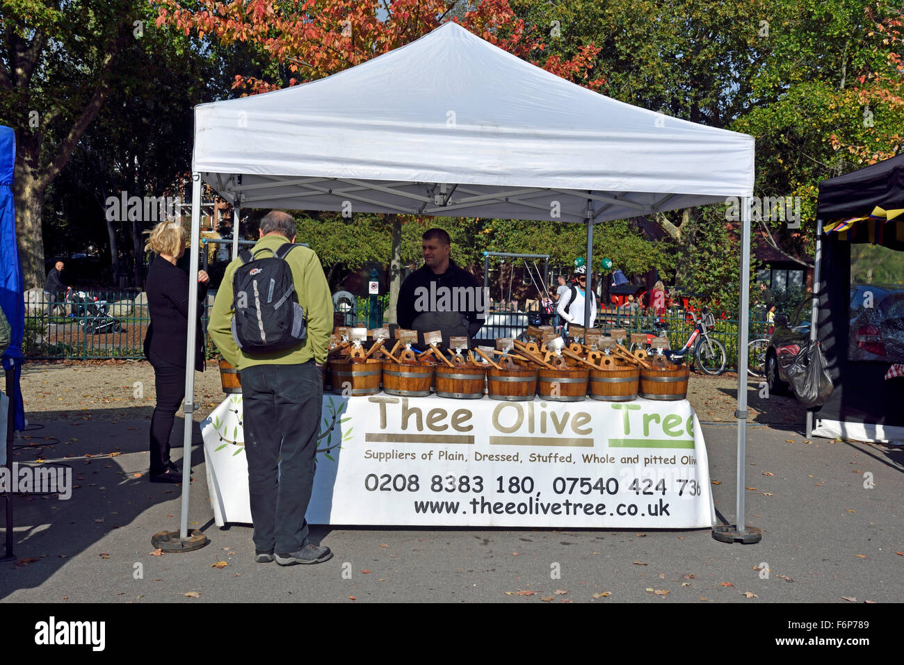 Man standing in front of Thee Olive Tree stall, Bishop's Park Farmer's Market London Borough of Hammersmith - Stock Image