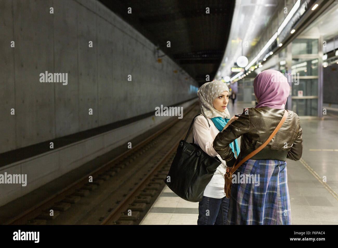 Female friends talking on railroad station platform - Stock Image