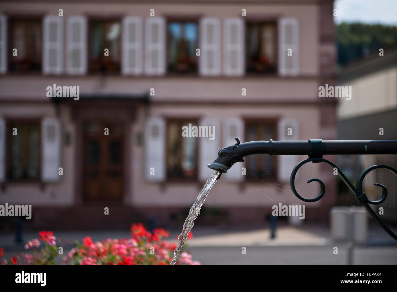 Fountain in the center of Sainte-Marie-aux-Mines which depicts the same fictitious creature on all 4 sides. Stock Photo