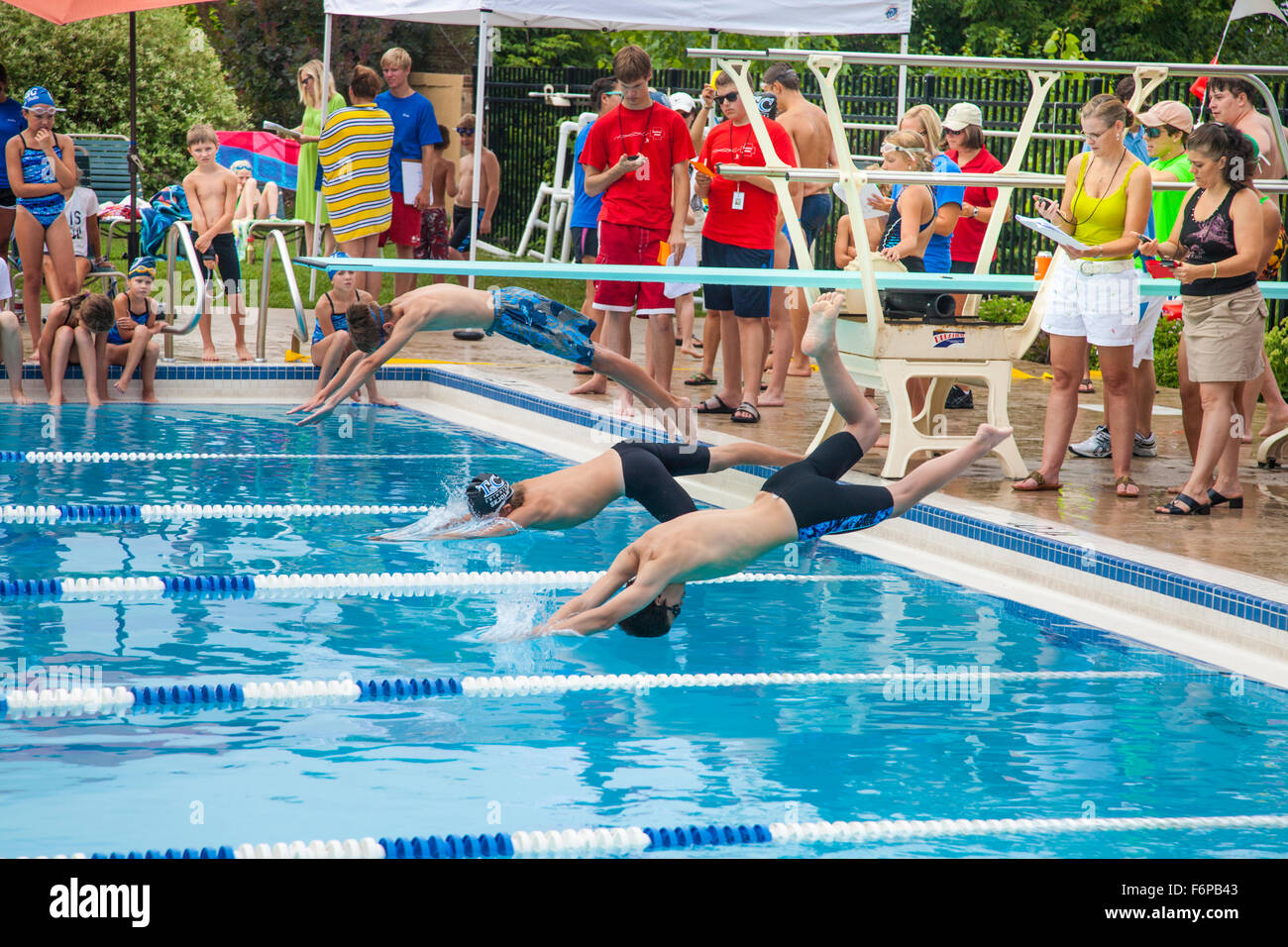 Boys age 12 diving into pool water participating in swim meet. St Paul Minnesota MN USA - Stock Image
