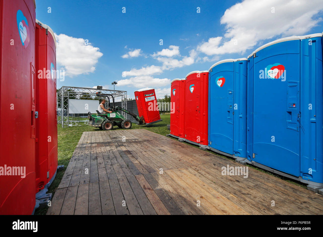 Placement of rows of colourful portable toilets at outdoor event - Stock Image