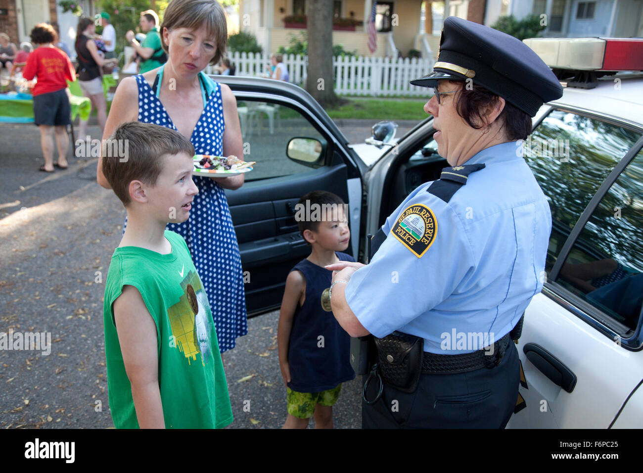 Auxiliary reserve police woman talking to boy age 9, neighborhood 'take back the night' street party. St - Stock Image
