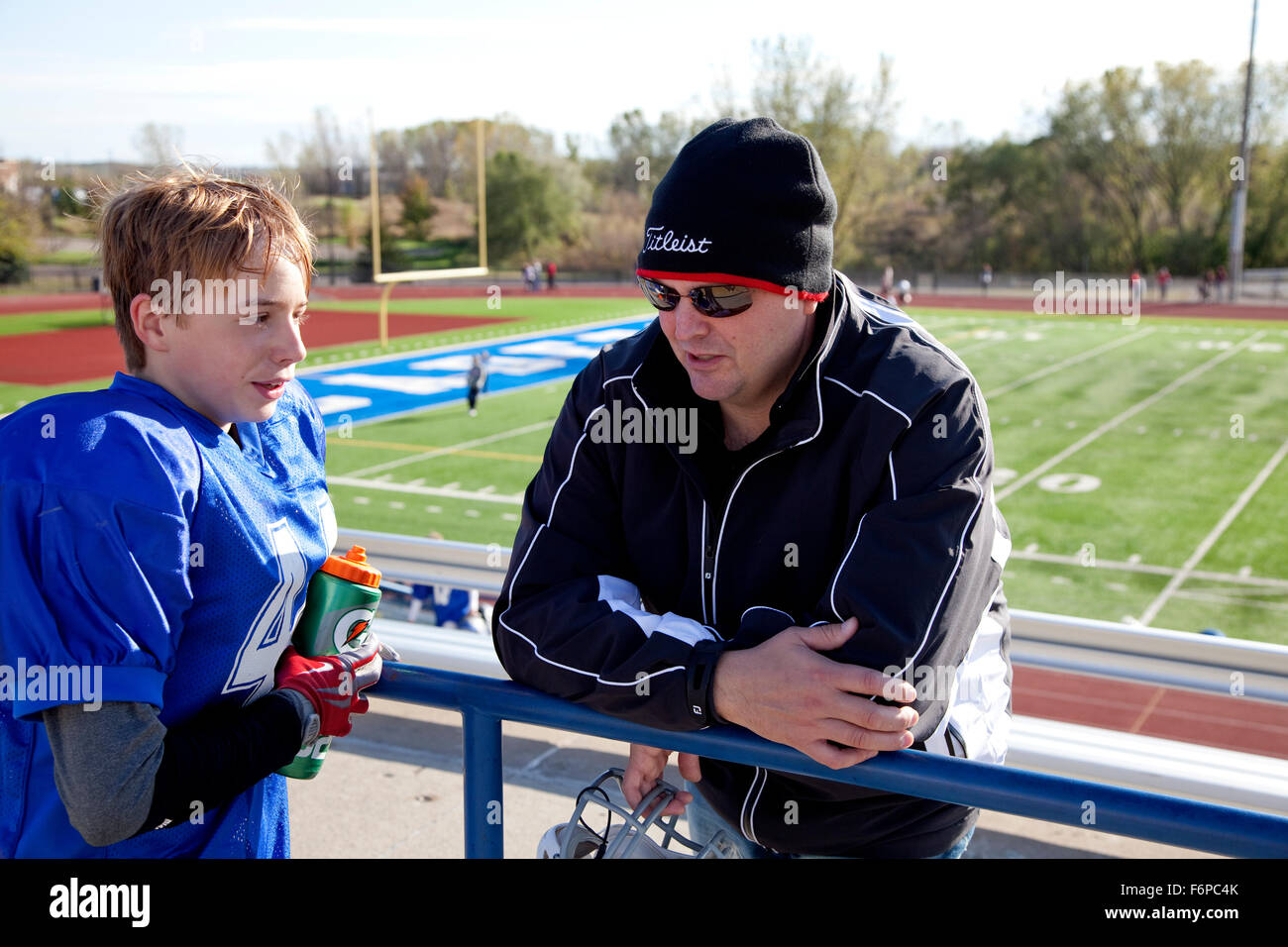 Dad talking to football player son age 12 after the game. Mendota Heights Minnesota MN USA - Stock Image