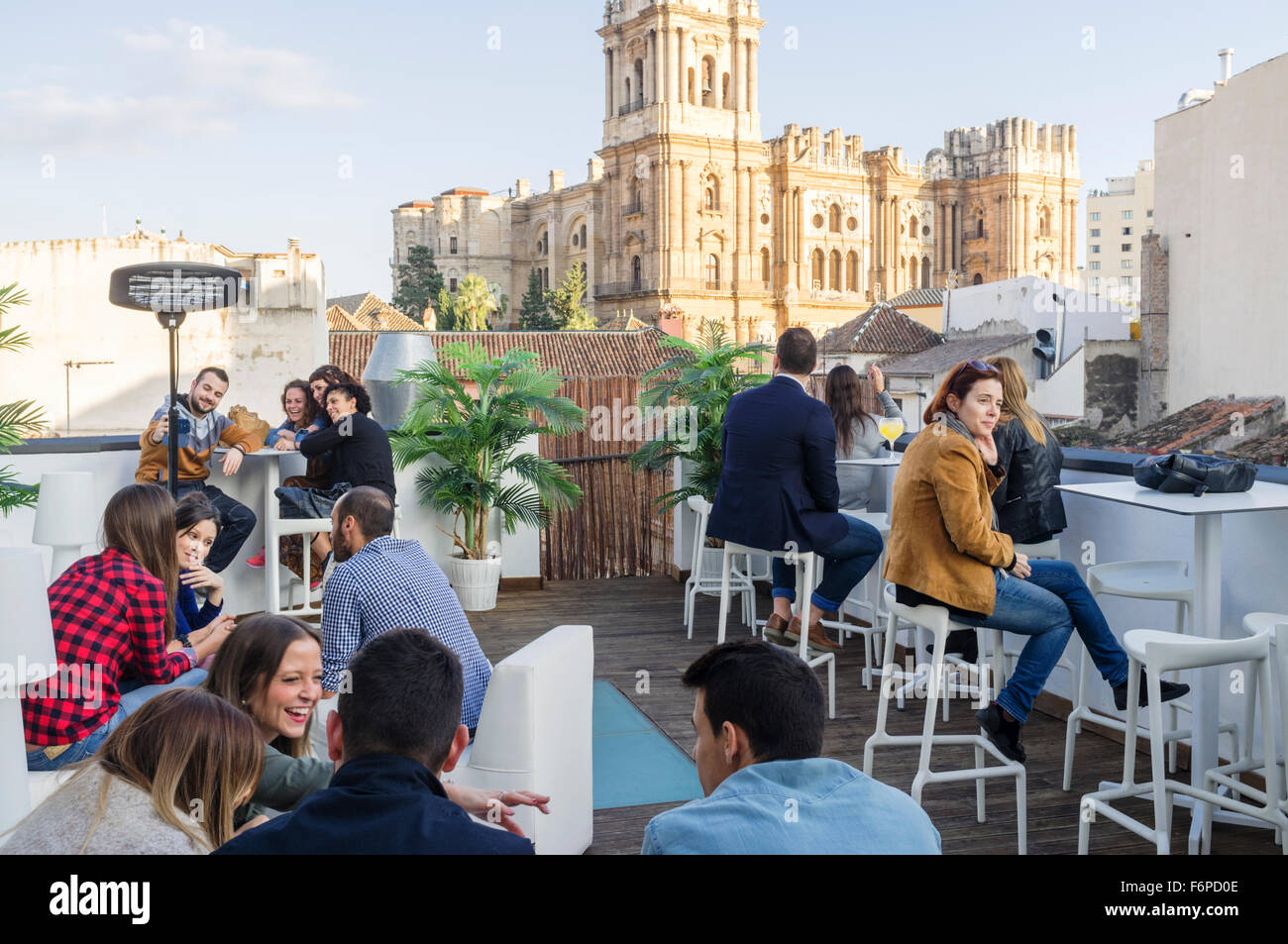 People at outdoors rooftop bar of Chinitas Urban Hostel with Cathedral in background. Malaga, Andalusia, Spain - Stock Image