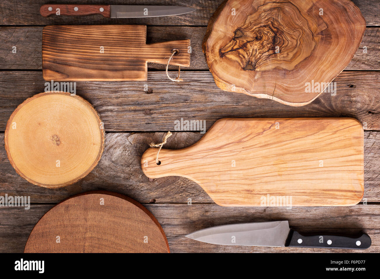 Wooden background with plenty of cutting boards and knifes - Stock Image