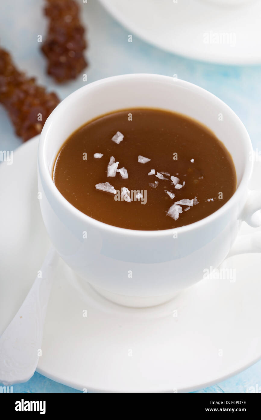 Caramel pudding in white cups with flaked salt - Stock Image