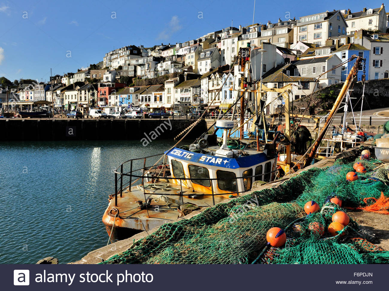 A fishing boat with fishing nets on the Quayside in Brixham Harbour, Devon - Stock Image
