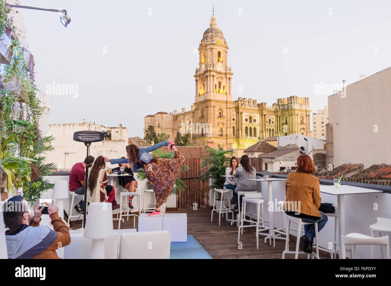 People at rooftop terrace bar with illuminated Cathedral in background. Malaga, Andalusia, Spain - Stock Image