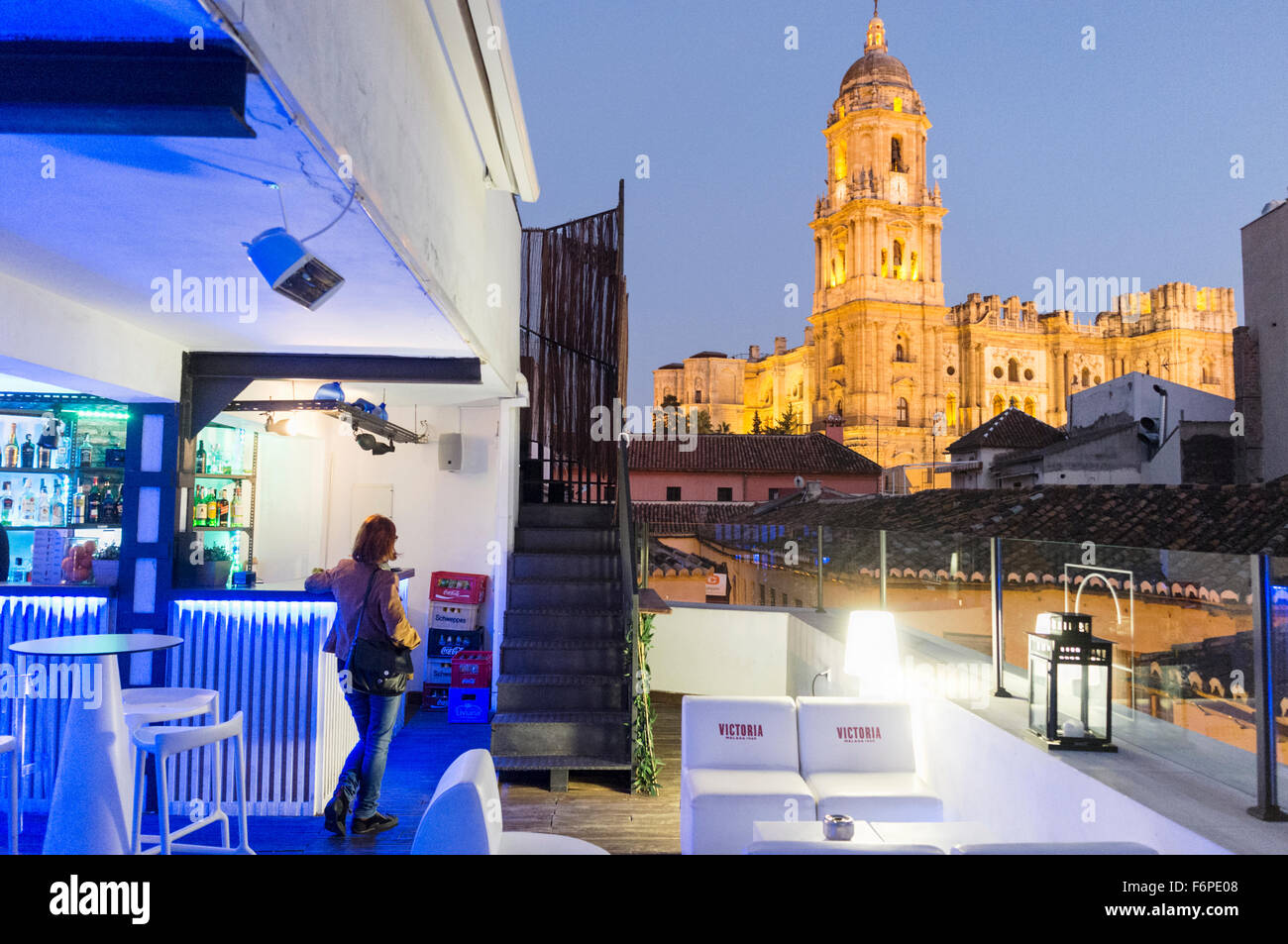 Woman at Chinitas Urban Hostel rooftop terrace bar with illuminated Cathedral in background. Malaga, Andalusia, - Stock Image